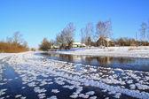 Winter village on coast river — Stock Photo