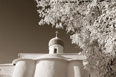 Tree in snow against christian church, sepia — Stock Photo