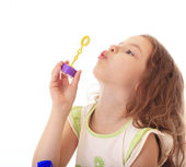 Beautiful little girl blow bubbles. — Stock Photo