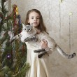 Beautiful girl with a cat near a Christmas tree. — Stock Photo