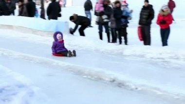 Joyful child rolls off the ice slide — Vídeo de Stock