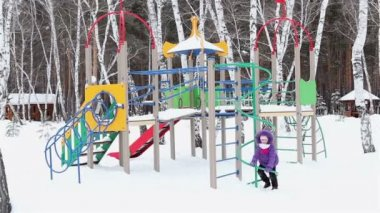 Little girl playing on the playground in winter. — Stock Video