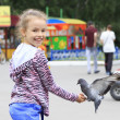 Joyful little girl with a dove on hand (feeding birds seeds) — Stock Photo #28317119