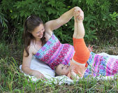 Beautiful pregnant woman playing with her little daughter — Stock Photo