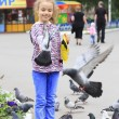 Joyful little girl with a dove on hand (feeding birds seeds) — Stock Photo #29782809