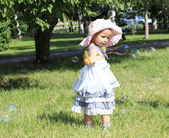 Little girl blowing soap bubbles in a city park. — Stock Photo