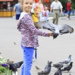 Joyful little girl with a dove on hand (feeding birds seeds) — Stock Photo