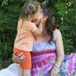 Little girl tenderly kisses and hugs his mother. — Stock Photo
