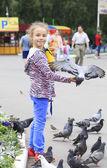 Joyful little girl with a dove on hand (feeding birds seeds) — Стоковое фото