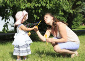 Beautiful mother and daughter blow bubbles in a city park. — Stock Photo
