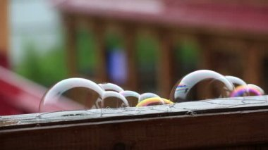 Soap bubbles on wet wooden veranda railing. — Stock Video