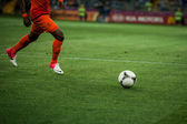 A soccer ball being kicked by the foot of a soccer player on the — Stock Photo