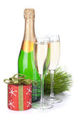 Champagne bottle, glasses and christmas decor — Stock Photo