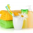 Toothbrushes, shampoo bottles, two towels and flower — Stock Photo #13590221