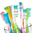 Colorful toothbrushes in glass - Stock Photo