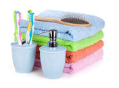 Four toothbrushes, liquid soap, hairbrush and colorful towels — Stock Photo