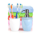 Four colorful toothbrushes, liquid soap and towels — Stock Photo