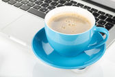 Blue coffee cup and laptop — Stock Photo