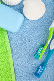 Toothbrushes and soap over towels — Stock Photo