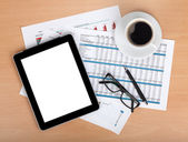 Tablet with blank screen over papers with numbers and charts — Foto Stock