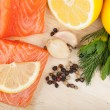 Salmon on cutting board with lemons and herbs — Stock Photo #23182760
