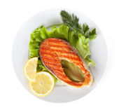 Grilled salmon with lemon slices and herbs on plate — Stock Photo
