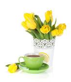 Gele tulpen en thee beker met citroen segment — Stockfoto