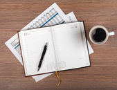 Notepad and coffee cup on wood table — Stock Photo