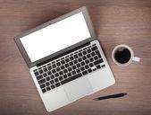 Laptop a káva pohár na dřevěný stůl — Stock fotografie