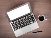 Laptop en koffie cup op houten tafel — Stockfoto