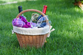 Outdoor picnic basket with wine on lawn — Stock Photo