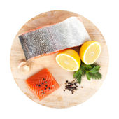 Salmon with herbs and lemon slices on cutting board — Stock Photo