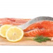 Salmon steaks on cutting board with lemons and herbs — Stock Photo