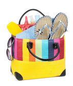 Bag with towels, sunglasses, flip-flops and beach items — Stock Photo