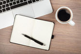 Notepad, laptop and coffee cup on wood table — Stock Photo