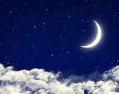 Moon and stars in a cloudy night blue sky — 图库照片