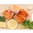 Grilled salmon with lemon slices and parsley on cutting board — Stock Photo #32171887