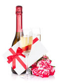 Champagne bottle and red rose flowers — Stock Photo