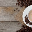 Coffee cup and beans on wooden table — Stock Photo #33556383