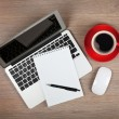 Foto Stock: Blank notepad over laptop and coffee cup