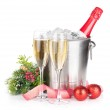 Champagne bottle in ice bucket, two glasses and christmas decor — Stock Photo
