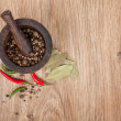Mortar and pestle with red hot chili pepper and peppercorn — Stock Photo #35665545