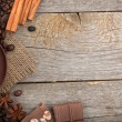 Coffee cup with spices and chocolate on wooden table texture — Stock Photo