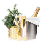 Champagne bottle in ice bucket, two glasses and christmas gift — Stock Photo