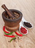 Mortar and pestle with red hot chili pepper and peppercorn — Stok fotoğraf