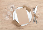 Blank paper on plate, wine glasses and silverware set — Stock Photo