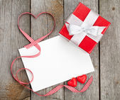 Greeting card and small red gift box — Stock Photo