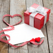 Blank valentines greeting card and small red gift box — Stock Photo