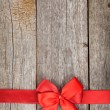 Wooden background with red bow and ribbon — Stock Photo #39132133