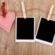 Blank instant photos and red heart hanging on clothesline — Stock Photo #39132153
